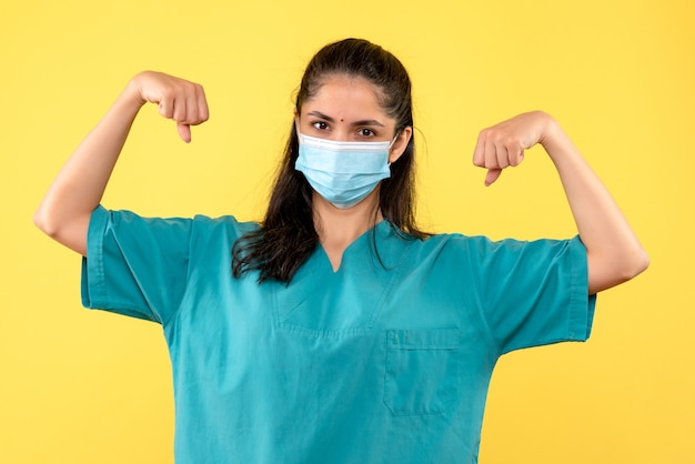 Vooraanzicht vrouwelijke arts toont haar spieren staan