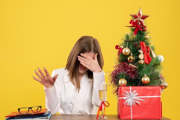 Vooraanzicht vrouwelijke arts zit achter haar tafel benadrukt op gele achtergrond met kerstboom en geschenkdozen