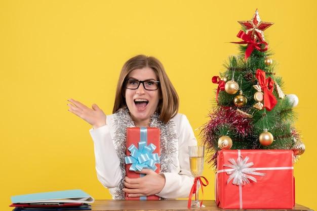 Vooraanzicht vrouwelijke arts zit tafel met cadeautjes en boom op gele achtergrond met kerstboom en geschenkdozen
