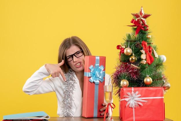 Vooraanzicht vrouwelijke arts zit tafel met cadeautjes en boom op gele achtergrond