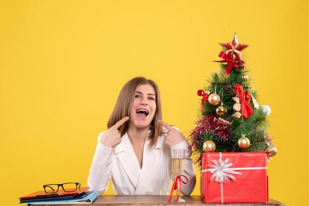 Vooraanzicht vrouwelijke arts zit tafel met kerstcadeautjes en boom op gele achtergrond