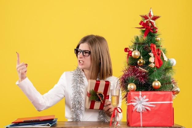 Vooraanzicht vrouwelijke arts zit voor haar tafel bedrijf aanwezig op gele achtergrond met kerstboom en geschenkdozen