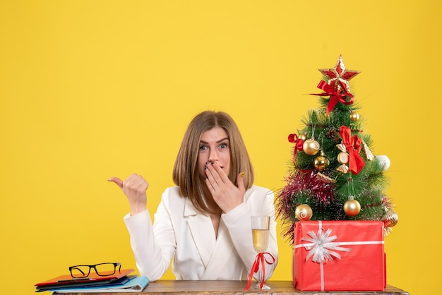 Vooraanzicht vrouwelijke arts zit voor haar tafel op de gele achtergrond ziekenhuis nieuwjaar kerst gezondheid emotie kleur
