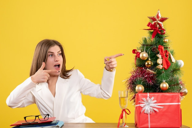 Vooraanzicht vrouwelijke arts zit voor haar tafel op gele achtergrond met kerstboom en geschenkdozen