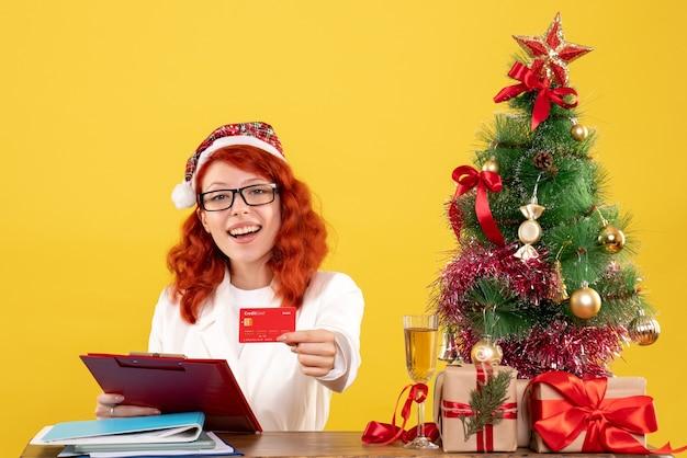 Vooraanzicht vrouwelijke arts zittend achter haar tafel en bankkaart op gele achtergrond met kerstboom en geschenkdozen te houden