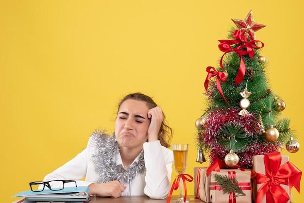 Vooraanzicht vrouwelijke arts zittend achter haar tafel en huilen op gele achtergrond met kerstboom en geschenkdozen
