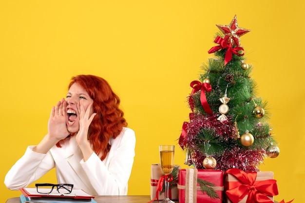 Vooraanzicht vrouwelijke arts zittend achter haar tafel met kerstcadeautjes en boom die gele achtergrond oproepen