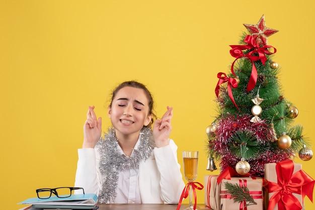 Vooraanzicht vrouwelijke arts zittend achter haar tafel op gele achtergrond met kerstboom en geschenkdozen