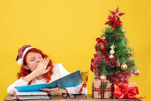 Vooraanzicht vrouwelijke arts zittend achter tafel documenten lezen en geeuwen op gele achtergrond met kerstboom en geschenkdozen