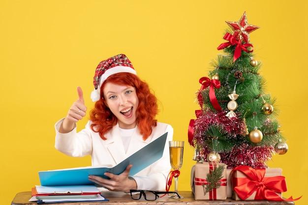 Vooraanzicht vrouwelijke arts zittend achter tafel documenten op de gele achtergrond met kerstboom en geschenkdozen te lezen