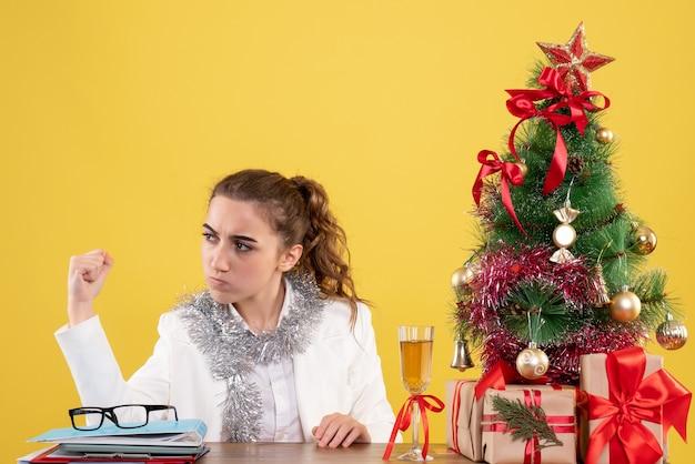 Vooraanzicht vrouwelijke arts zittend achter tafel met kerstcadeautjes en boom op geel bureau