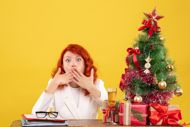 Vooraanzicht vrouwelijke arts zittend achter tafel met kerstcadeautjes geschokt op gele achtergrond