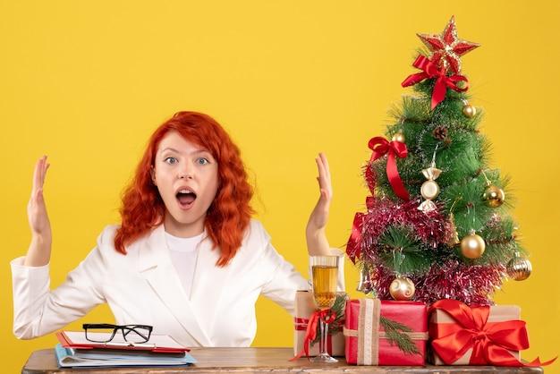 Vooraanzicht vrouwelijke arts zittend achter tafel met kerstcadeautjes op geel