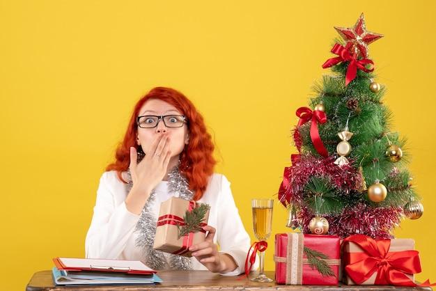 Vooraanzicht vrouwelijke arts zittend achter tafel met kerstcadeautjes op gele achtergrond