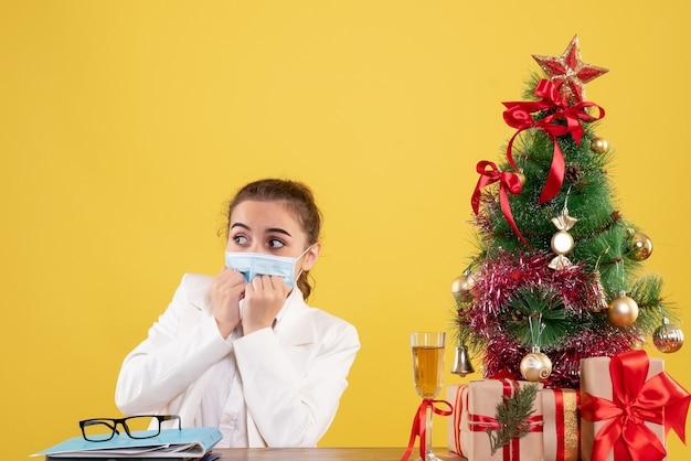 Vooraanzicht vrouwelijke arts zittend in beschermend masker op gele achtergrond met kerstboom en geschenkdozen