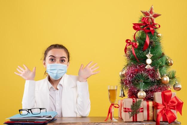 Vooraanzicht vrouwelijke arts zittend in steriel masker op gele achtergrond met kerstboom en geschenkdozen
