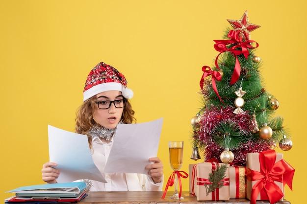 Vooraanzicht vrouwelijke arts zittend met kerst presenteert boom en documenten op gele achtergrond te houden