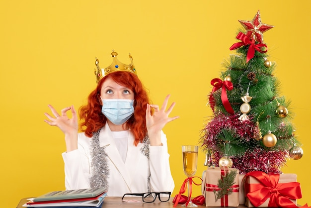 Vooraanzicht vrouwelijke arts zittend met kerstcadeautjes en het dragen van kroon op gele achtergrond