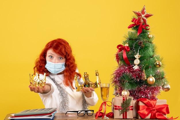 Vooraanzicht vrouwelijke arts zittend met kerstcadeautjes en kronen op gele achtergrond te houden