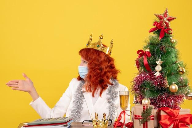 Vooraanzicht vrouwelijke arts zittend met kerstcadeautjes groet op gele achtergrond