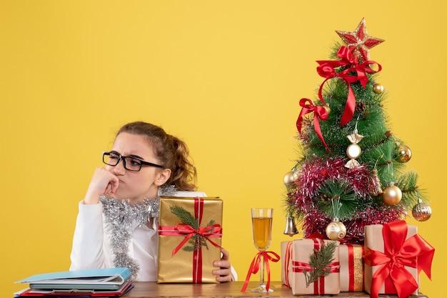 Vooraanzicht vrouwelijke arts zittend rond kerstcadeautjes en boom denken op lichtgele achtergrond