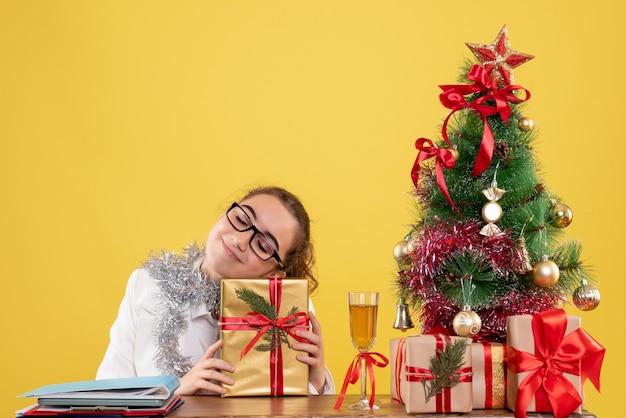 Vooraanzicht vrouwelijke arts zittend rond kerstcadeautjes en boom met opgetogen gezicht op gele achtergrond