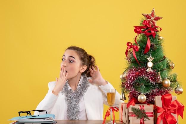 Vooraanzicht vrouwelijke arts zittend rond kerstcadeautjes en boom op gele achtergrond