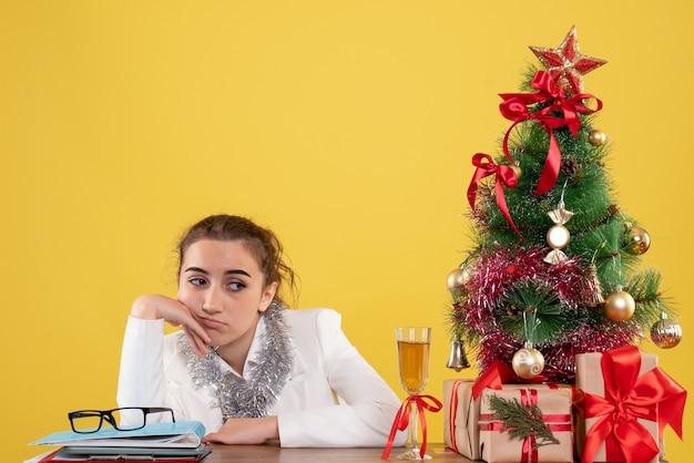 Vooraanzicht vrouwelijke arts zittend rond kerstcadeautjes en boom verveeld gevoel op gele achtergrond