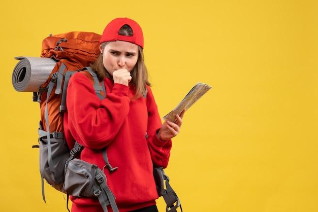 Vooraanzicht vrouwelijke backpacker die reiskaart steunt