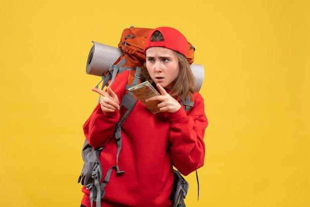 Vooraanzicht vrouwelijke backpacker met reiskaart wijzende vinger iets