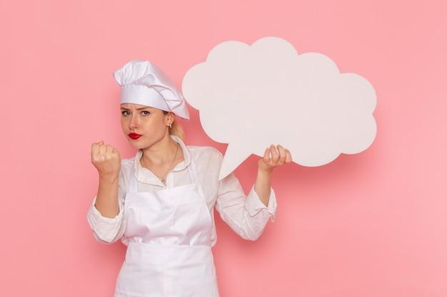 Vooraanzicht vrouwelijke banketbakker in witte slijtage met een groot wit bord boos bedreigend op de roze muur kok baan keuken keuken eten