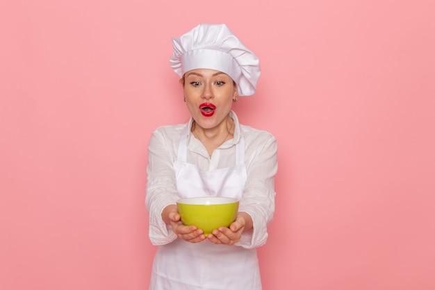 Vooraanzicht vrouwelijke banketbakker in witte slijtage met groene plaat met dovga onpink wall maaltijd greens groente