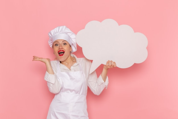 Vooraanzicht vrouwelijke banketbakker in witte slijtage met groot wit bord op de roze muur kookbaan keuken keuken eten