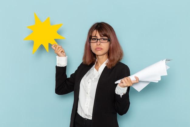 Vooraanzicht vrouwelijke beambte in strikt pak met geel bord en documenten op blauwe ondergrond