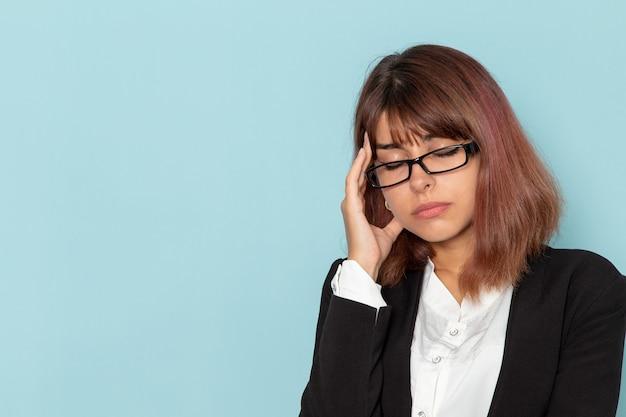 Vooraanzicht vrouwelijke beambte in strikt pak met hoofdpijn op blauwe ondergrond