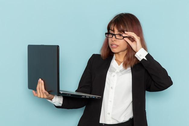 Vooraanzicht vrouwelijke beambte in strikte pak met behulp van laptop op blauwe ondergrond