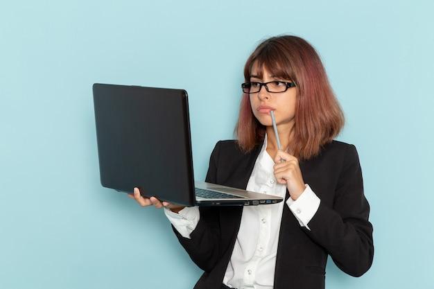 Vooraanzicht vrouwelijke beambte in strikte pak met behulp van laptop op het lichtblauwe oppervlak
