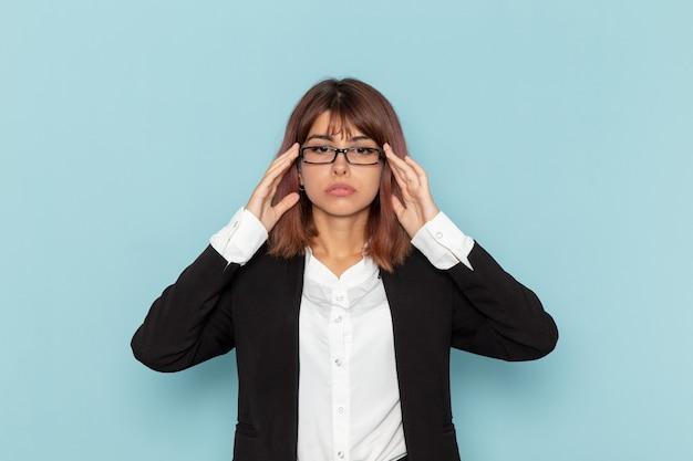 Vooraanzicht vrouwelijke beambte poseren en haar optische zonnebril op lichtblauwe ondergrond aan te raken
