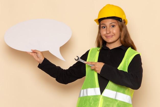 Vooraanzicht vrouwelijke bouwer die in gele helm een groot wit teken zilveren hulpmiddel op witte bureau vrouwelijke architect houdt