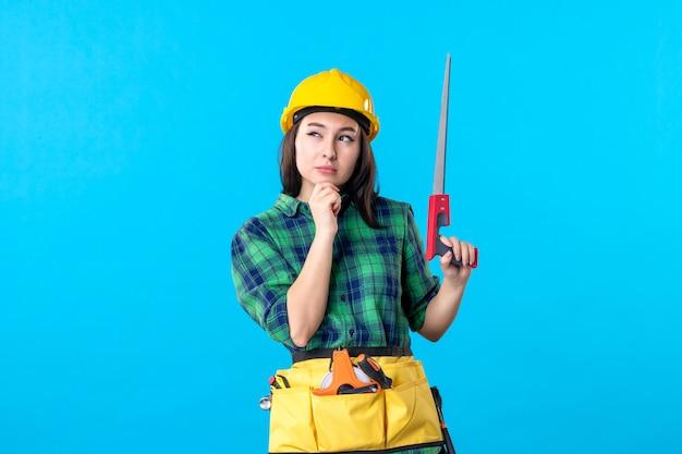 Vooraanzicht vrouwelijke bouwer die kleine zaag op blauw houdt