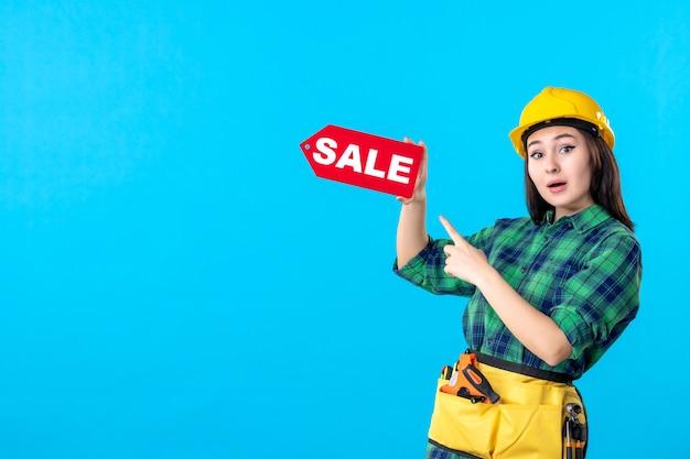Vooraanzicht vrouwelijke bouwer die rode verkoop houdt die op blauw schrijft