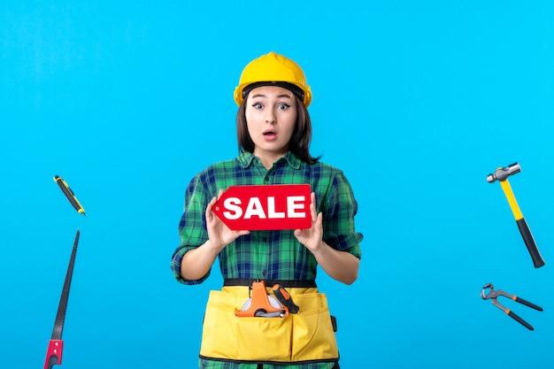 Vooraanzicht vrouwelijke bouwer die verkoop houdt die op een blauw schrijft