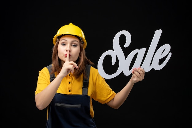 Vooraanzicht vrouwelijke bouwer die wit verkoopteken op zwarte muur houdt