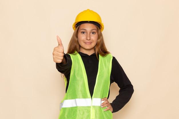 Vooraanzicht vrouwelijke bouwer in geel helm zwart shirt glimlachend tonen als teken op de witte muur