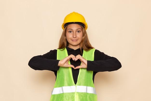 Vooraanzicht vrouwelijke bouwer in geel helm zwart shirt met hartteken op de witte muur