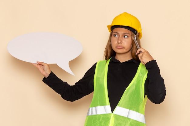 Vooraanzicht vrouwelijke bouwer in gele helm die een groot wit teken zilveren hulpmiddel houdt die op wit bureauwijfje denken