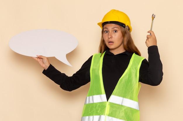 Vooraanzicht vrouwelijke bouwer in gele helm die een groot wit teken zilveren hulpmiddel op de vrouwelijke architect van de witte muur houdt