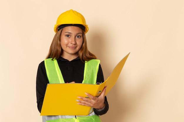 Vooraanzicht vrouwelijke bouwer in gele helm die geel dossier houdt dat nota's opschrijft die op witte muur glimlachen