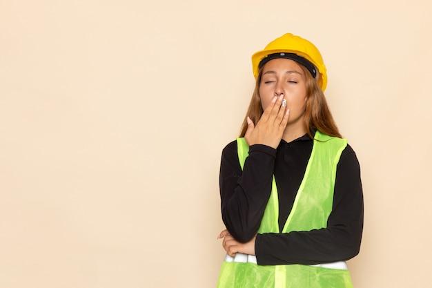 Vooraanzicht vrouwelijke bouwer in gele helm zwarte shirt poseren geeuwen op de witte muur