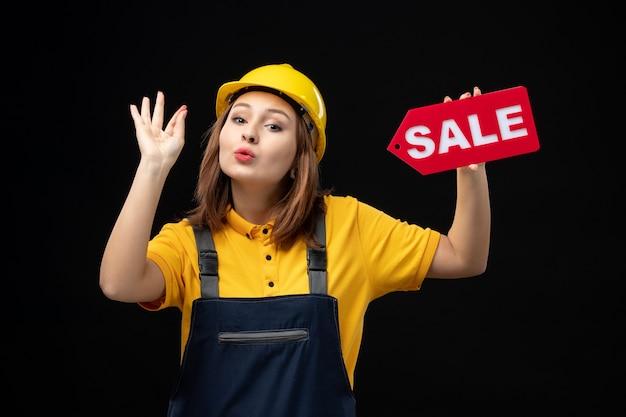 Vooraanzicht vrouwelijke bouwer in uniform bedrijf verkoop teken op zwarte muur
